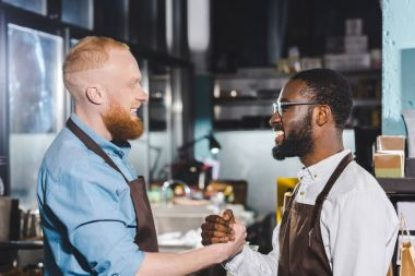 side view of two young multiethnic owners of coffee shop in aprons shaking hands in coffee shop