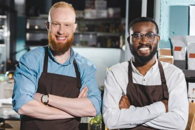 portrait of two young multiethnic owners of coffee shop in aprons standing with crossed arms in coffee shop