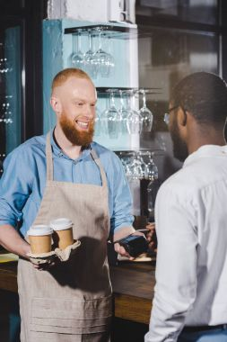 african american man paying by credit card and smiling male barista with terminal and paper cups of coffee