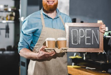 cropped shot of young male barista holding chalkboard with lettering open and two papers cups of coffee