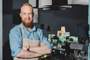 confident bearded barista in apron standing with crossed arms and smiling at camera in coffee shop