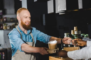 cropped shot of smiling bearded young barista giving paper bag and disposable coffee cups to african american buyer in cafe