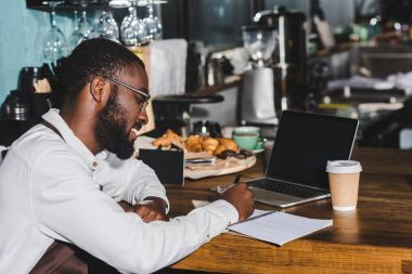 smiling young african american barista in eyeglasses taking notes and using laptop with blank screen in cafe