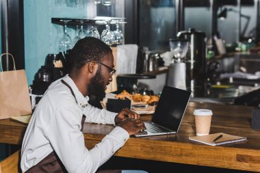 smiling young african american barista in eyeglasses using laptop in coffee shop