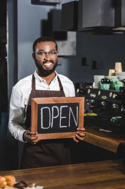handsome young african american barista in eyeglasses holding sign open and smiling at camera in coffee shop