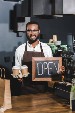 young african american barista in eyeglasses holding sign open and disposable paper cups, smiling at camera in coffee shop