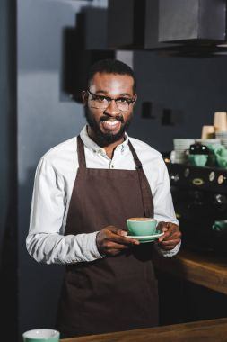 handsome african american barista in eyeglasses holding cup of cappuccino and smiling at camera