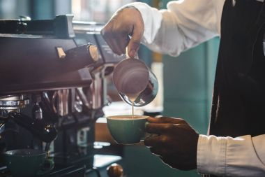 cropped shot of barista preparing cappuccino in coffee shop