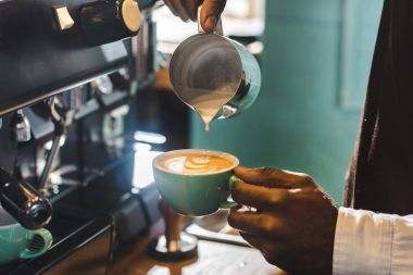 close-up partial view of barista preparing cappuccino in coffee shop
