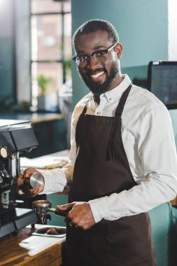 young african american barista in eyeglasses smiling at camera while making coffee at coffee machine