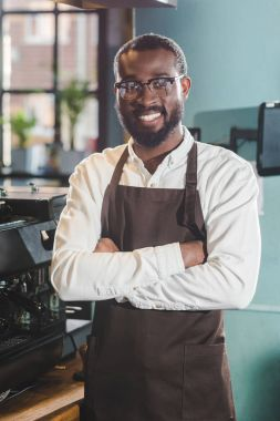 happy young african american barista standing with crossed arms and smiling at camera in coffee shop