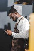 a fiatal afroamerikai csapos használ smartphone kávézóban oldalnézete