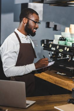 smiling young african american barista in eyeglasses taking notes while woeking in cafe