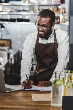 happy young african american barista taking notes and using laptop at coffee shop