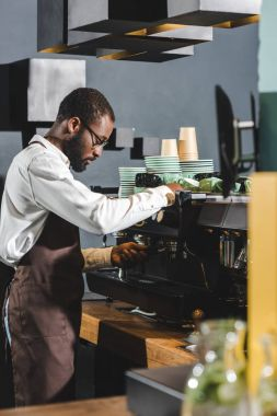 side view of african american barista in eyeglasses working with coffee machine