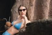 Fotografia ragazza attraente in occhiali da sole posa con cocco cocktail