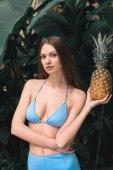 krásná mladá žena v modrých bikinách drží ananas na tropický resort