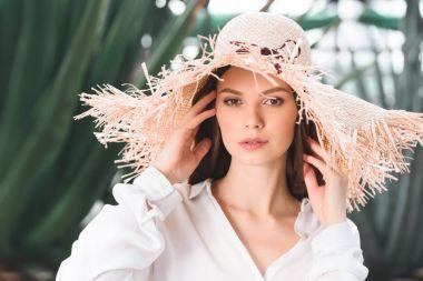 beautiful young woman in straw hat posing in tropical garden