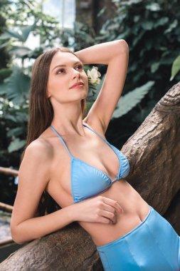 Beautiful slim model in blue bikini with flower in hair posing on tropical resort stock vector