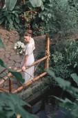 Fotografie Draufsicht auf attraktive Braut posiert in weißen Kleid mit Hochzeitsstrauß im tropischen Garten