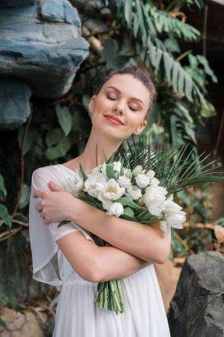 happy beautiful bride posing with wedding bouquet