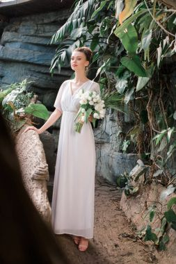 beautiful bride posing in white dress with wedding bouquet in tropical garden