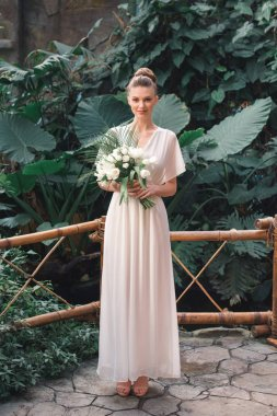 beautiful young bride posing in white dress with wedding bouquet in tropical garden