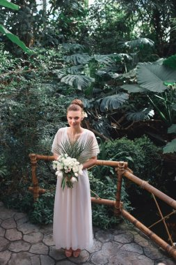 young bride posing in white dress with wedding bouquet in tropical garden