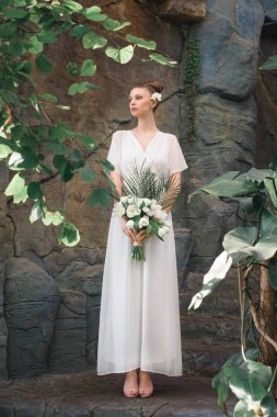 beautiful bride posing in white dress with wedding bouquet