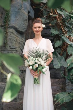 beautiful happy bride posing in white dress with wedding bouquet