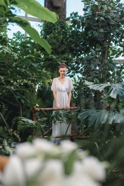 attractive woman in white dress posing in tropical garden