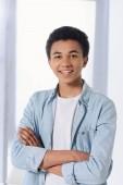 lächelnder afrikanisch-amerikanischer Teenager, der mit verschränkten Armen zu Hause in die Kamera schaut