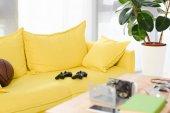 Fotografie gamepady a basketbalový míč na žluté pohovce doma