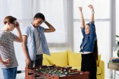 Photo happy teen kid winning table football at multicultural teenagers at home