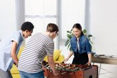 Photo multicultural teenagers playing table football at home