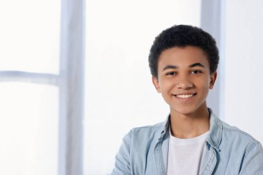 smiling african american teenager looking at camera at home
