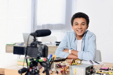 smiling african american teenager shooting video blog at home