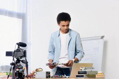 african american teenager preparing shooting tech video blog at home