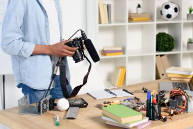 Cropped image of african american teenager holding digital camera for shooting vlog at home stock vector