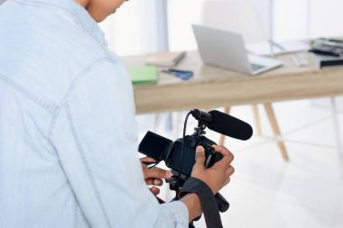 cropped image of african american teenager holding digital camera for shooting vlog at home