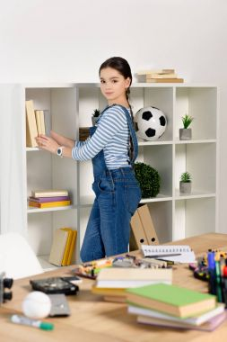 adorable preteen child putting books on shelf and looking at camera at home