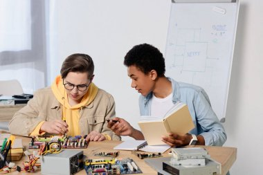 multicultural teen boys studying and repairing computer motherboard at home