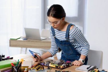 female teenager soldering computer motherboard with soldering iron at home