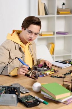 teen boy soldering computer circuit with soldering iron at home