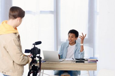 multicultural teen boys shooting video blog with camera at home