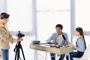 multicultural teenagers shooting video blog about engineering at home
