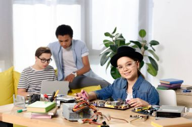 multicultural teen boys using laptop and female kid fixing computer motherboard at home