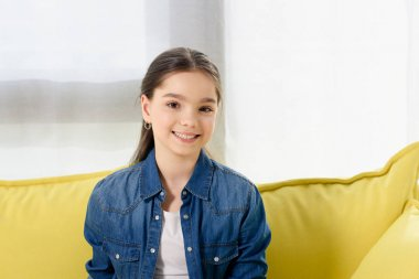 portrait of smiling preteen child looking at camera on sofa at home