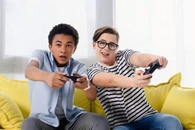 Multicultural teen boys playing video game at home stock vector