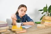 adorable preteen child touching potted plant at table with books at home